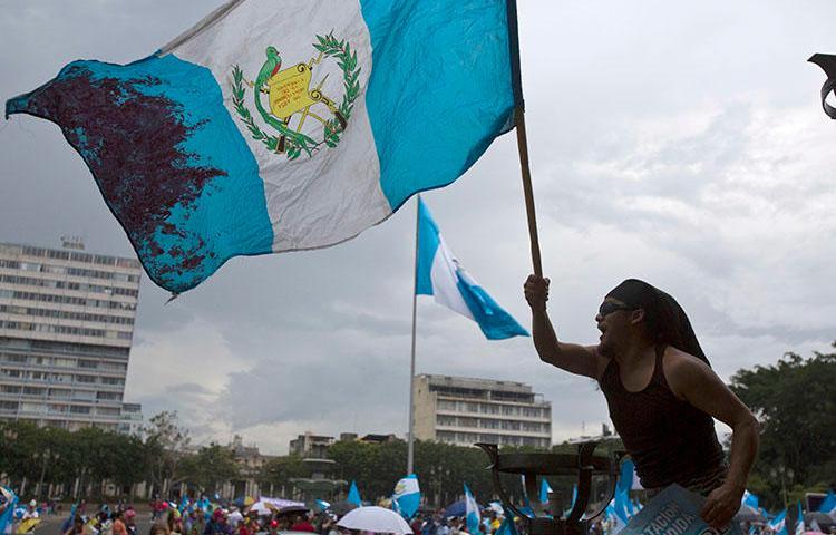 Un hombre ondea la bandera nacional de Guatemala durante una protesta en Ciudad de Guatemala. El país tiene previsto celebrar elecciones presidenciales y legislativas en Junio. (AP/Moisés Castillo, archivo) (AP/Moises Castillo, File)