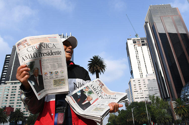 A vendor sells newspapers showing the results of Mexico's presidential elections, in Mexico City, in July 2018. Mexico's new government has said it will address the opaque practice of government advertising in media. (AFP/Ulises Ruiz)