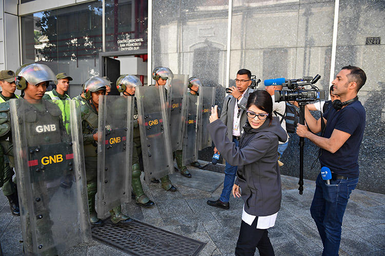 Members of the press and the Bolivarian National Guard, pictured outside the Federal Legislative Palace, in Caracas, on May 15, 2019. Local and international journalists say there are several challenges to covering the Venezuela crisis. (AFP/Ronaldo Schemidt)