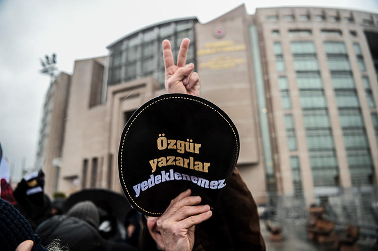 A man holds a sign reading 'Writers' freedom is not guaranteed' outside an Istanbul court during a trial connected to the now shuttered paper Özgür Gündem, in December 2016. A court sentenced seven former journalists from the paper to prison on May 21, 2019. (AFP/Ozan Kose)