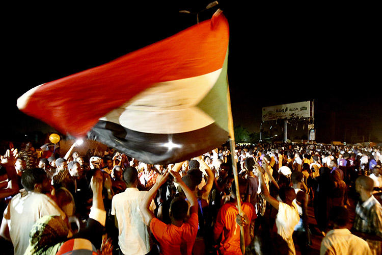 Sudanese wave flags and chant slogans as they gather outside the army headquarters in Khartoum on May 30. Sudan's military rulers have ordered Al-Jazeera's Khartoum bureau to be shut down. (AFP/Ashraf Shazly)
