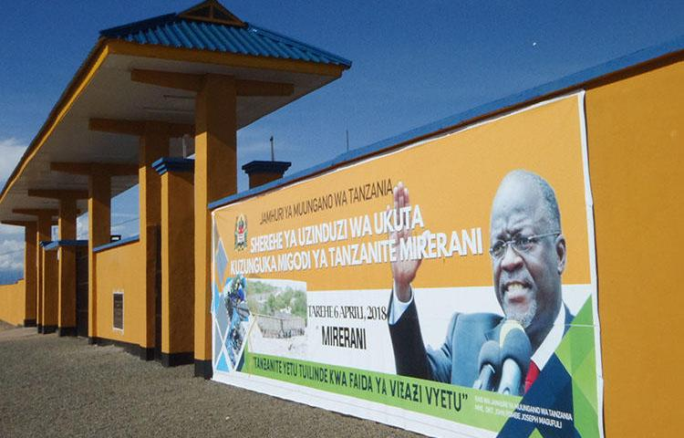A banner of Tanzanian President John Magufuli hangs on a wall around a tanzanite mine, in April 2018. CPJ and other organizations are calling on the Human Rights Council to address a crackdown on journalists, human rights defenders, and other groups in the country. (AFP/Joseph Lyimo)