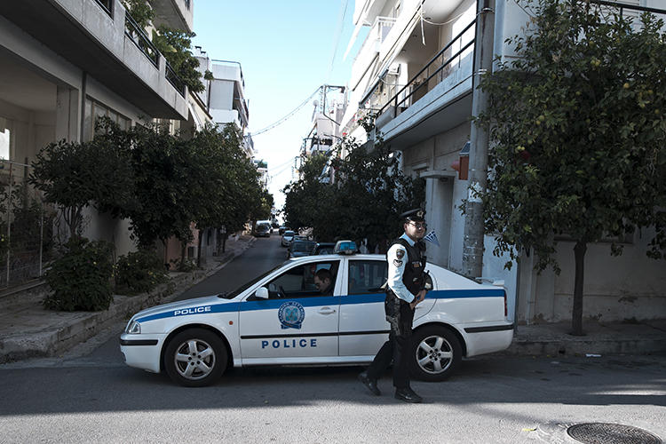 Police officers are seen in Athens, Greece, on November 13, 2018. CNN Greek reporter Mina Karamitrou's car was recently destroyed by a bomb in an Athens suburb. (AP/Petros Giannakouris)