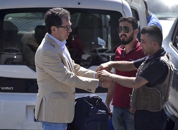 Kadri Gürsel, left, is handcuffed by police outside an Istanbul prison on May 29. Gürsel, a former columnist for Cumhuriyet, and Turkey chair of the International Press Institute, was freed later that day. (AP/DHA)