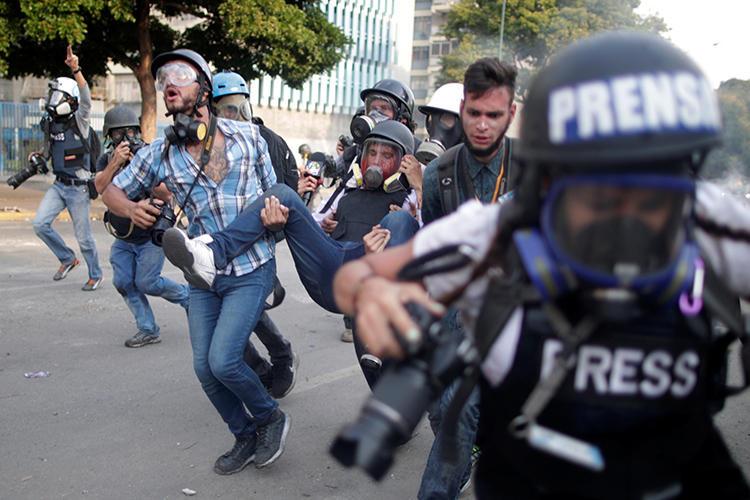 Un trabajador de la prensa herido es cargado durante una protesta contra el gobierno del Presidente Nicolás Maduro y para conmemorar el día del trabajador en Caracas, Venezuela, el 1ero de mayo, de 2019. (Reuters/Ueslei Marcelino)