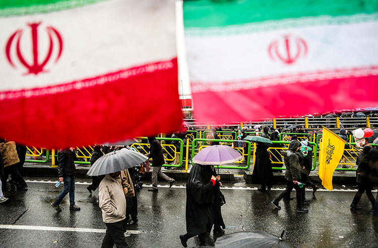 People carry umbrellas in Tehran, Iran, on February 11, 2019. On May 1, two journalists were arrested while covering Labor Day demonstrations in Tehran. (Vahid Ahmadi/Tasnim News Agency via Reuters)