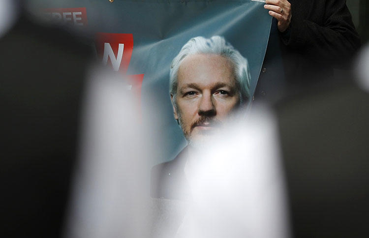 Police watch supporters of WikiLeaks founder Julian Assange protesting in London on June 14, 2019 before a scheduled court date in his fight against extradition to the United States, where he faces prosecution for conspiracy to commit computer intrusion, as well as the Espionage Act. (AP Photo/Frank Augstein)