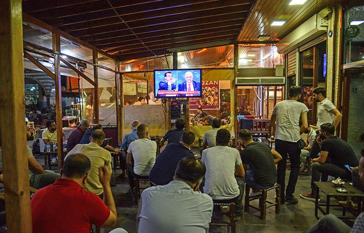 People watch a live broadcast of a televised debate between Istanbul's mayoral candidates at a tea house in Diyarbakir on June 16, 2019. (AFP/Ilyas Akengin)