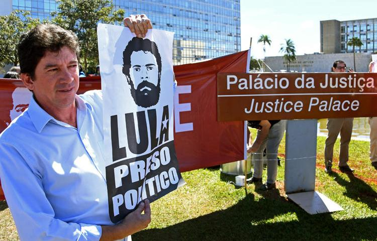 """Demonstrators protest in front of the Justice Ministry in Brasilia calling for the release of former President Luiz Inacio Lula da Silva and the arrest of Brazil's justice minister on June 10, 2019. The staff of 'The Intercept Brasil' received threats after publishing a report June 9 about the """"Operation Car Wash"""" corruption investigation of Lula and other politicians. (AFP/Evaristo Sa)"""
