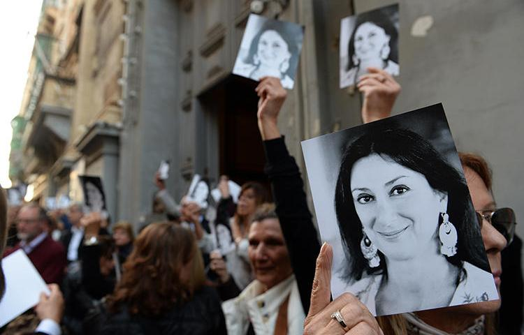 People are seen holding photos of journalist Daphne Caruana Galizia in Valletta, Malta, on April 16, 2018. The Parliamentary Assembly of the Council of Europe recently passed a resolution requiring the Maltese government to launch an independent public inquiry into her killing. (AFP/Matthew Mirabelli)