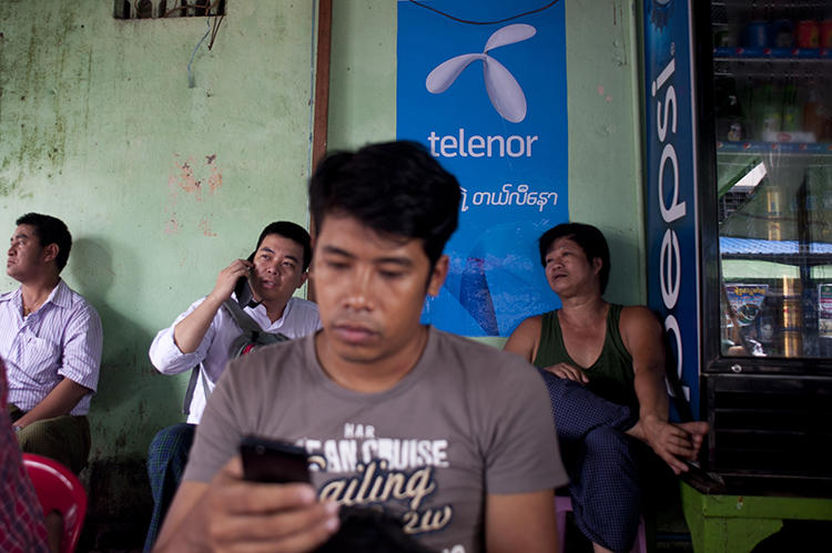 A man uses a cellphone in Yangon, Myanmar, on September 26, 2014. The government recently cut mobile internet access to Rakhine and Chin states. (AFP/Ye Aung Thu)