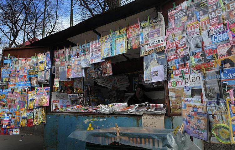 A man waits for customers in a news kiosk in Bucharest, Romania, on March 22, 2011. Romanian investigative journalist Diana Oncioiu received an anonymous death threat on June 11, 2019. (AFP/Daniel Mihailescu)