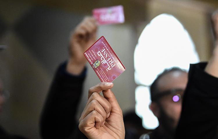 Journalists hold press cards during a protest at the Assembly of the Representatives of the People in Tunis in April 2019. Tunisia has greater press freedom but challenges remain. (AFP/Fethi Belaid)