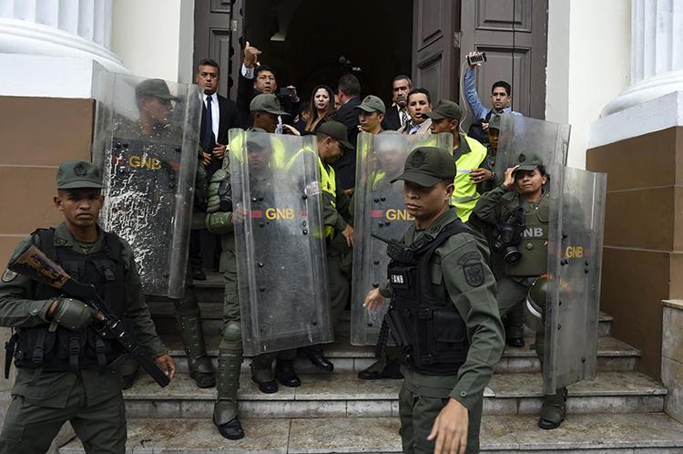 Miembros de la Guardia Nacional Bolivariana impiden a los periodistas entrar a la Asamblea Nacional, en Caracas, Venezuela, el 18 de junio de 2019. Los oficiales han bloqueado la entrada de los periodistas al edificio de la Asamblea durante los debates celebrados los días martes, desde el 7 de mayo. (AFP/Yuri Cortez)