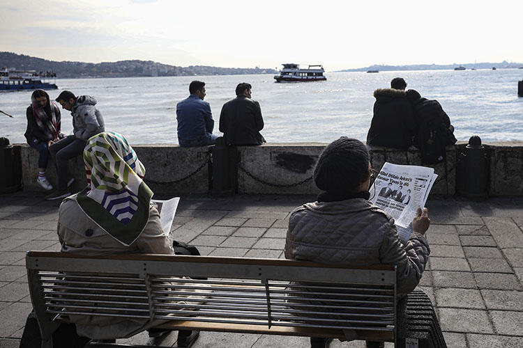 People read papers by the Bosporus in Istanbul in April 2019. A journalist this week started a prison sentence for insulting Turkey's president in a speech. (AP/Emrah Gurel)