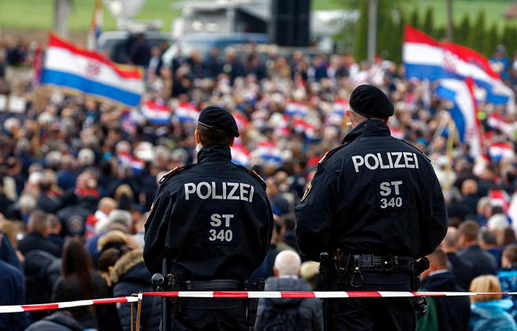 Austrian police, pictured at a World War II memorial in Bleiburg on May 18, 2019, that was attended by thousands of Croatian far-right supporters. A Croatian journalist says he was harassed and assaulted during the event. (AP/Darko Bandic)