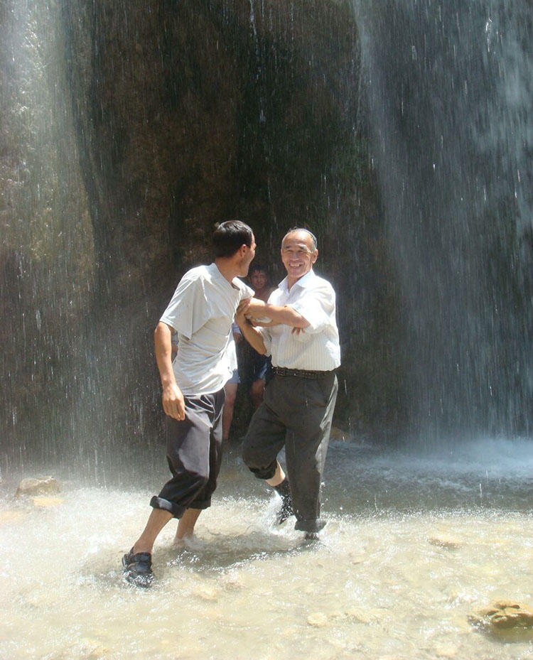 Azimjon Askarov and his son, pictured during a family vacation in 2009. Askarov's wife says the journalist used to be full of energy but his long imprisonment has left him sickly. (Askarov family)