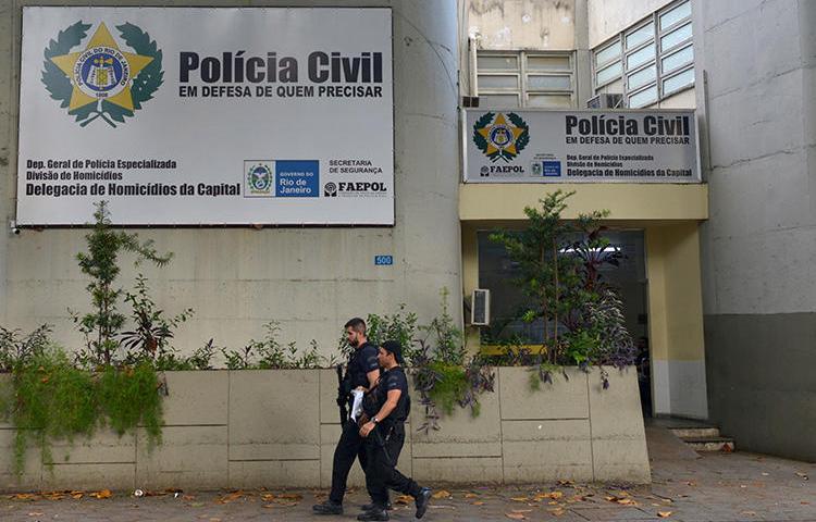 Policiais caminham em frente ao departamento de homicídios no Rio de Janeiro, Brasil, em 13 de março de 2019. O jornalista Romário Barros foi morto recentemente em Maricá, no estado do Rio de Janeiro. (Reuters / Lucas Landau)