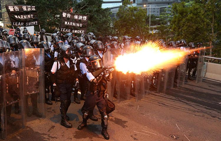 Police officers fire tear gas in Hong Kong on June 12, 2019. CPJ has called on Hong Kong authorities to investigate police actions against journalists during the city's ongoing protests. (Reuters/Athit Perawongmetha)
