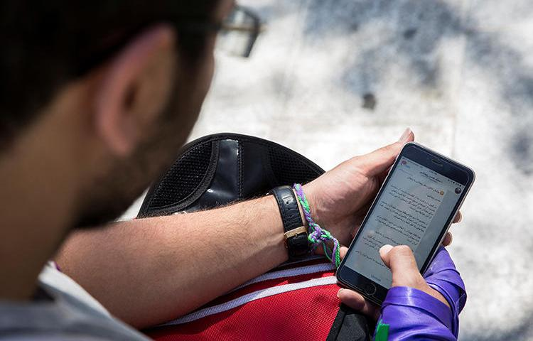 A man uses his smartphone to follow election news in Tehran, Iran, May 17, 2017. Iran charged four Telegram news channel Gam reporters over labor coverage, it was reported June 11. (Reuters/TIMA)