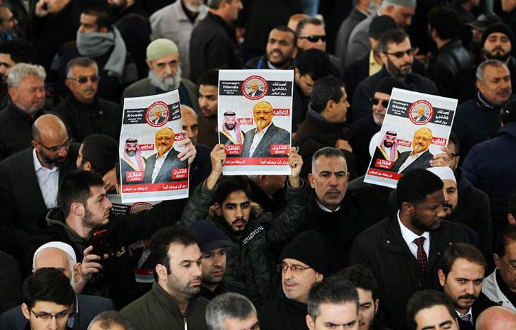 People holding pictures of murdered Saudi journalist Jamal Khashoggi during a symbolic funeral prayer held in Istanbul, Turkey on November 16, 2018. (REUTERS/Huseyin Aldemir)