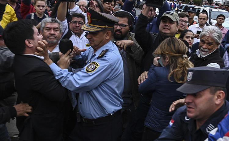 Un periodista es agarrado por un agente policial durante las protestas en Asunción, Paraguay, el 23 de julio de 2019. Por lo menos cuatro periodistas resultaron heridos durante las protestas, y una periodista fue presuntamente manoseada por un manifestante.  (AFP/Norberto Duarte)