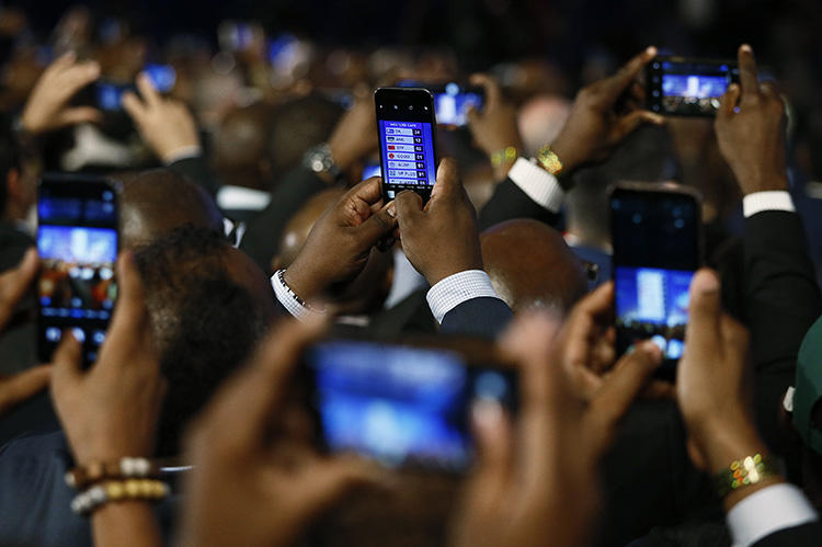 People take pictures with cells phones during the formal announcement of election results in Pretoria on May 11. Journalists covering the election had to contend with online harassment, doxxing, and threats. (AFP/Phill Magakoe)