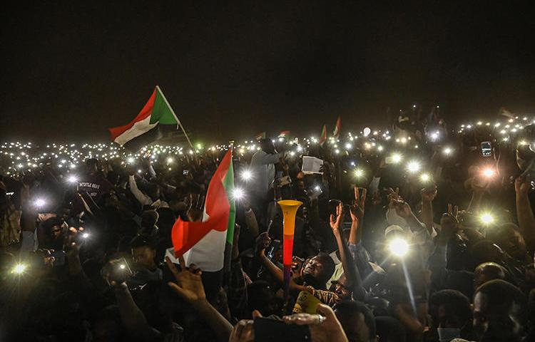 Sudanese protesters are seen with their smartphones in Khartoum on April 21, 2019. CPJ has called on South African telecommunications company MTN Group to end its role in Sudan's internet shutdowns. (AFP/Ozan Kose)