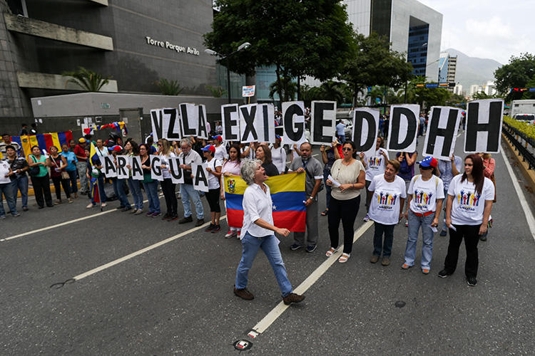 Opposition supporters demonstrate outside the headquarters of the U.N. Development Programme during the visit of UN High Commissioner for Human Rights Michelle Bachelet, in Caracas on June 21, 2019. Venezuelan journalist Braulio Jatar was conditionally released from house arrest on July 8, 2019, and barred from the leaving country. (AFP/Cristian Hernandez)