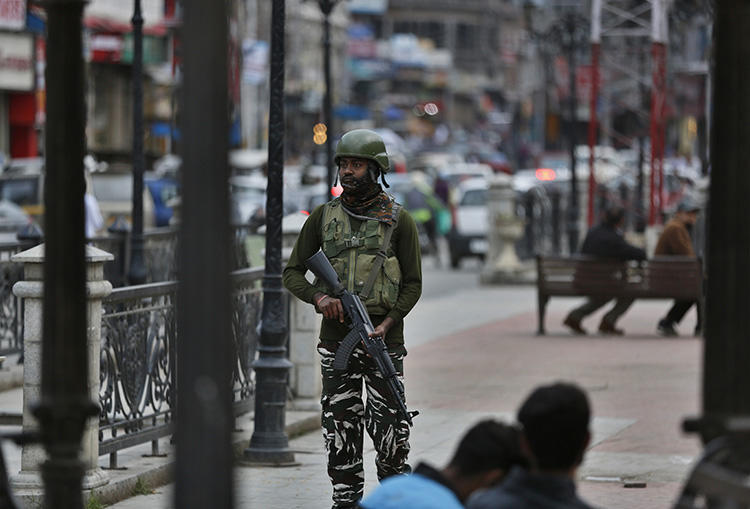 An Indian paramilitary soldier stands guard in Srinagar, Indian-controlled Jammu and Kashmir, on June 12, 2019. India's National Investigation Agency questioned Greater Kashmir editor Fayaz Kaloo for six days in early July. (AP Photo/Mukhtar Khan)