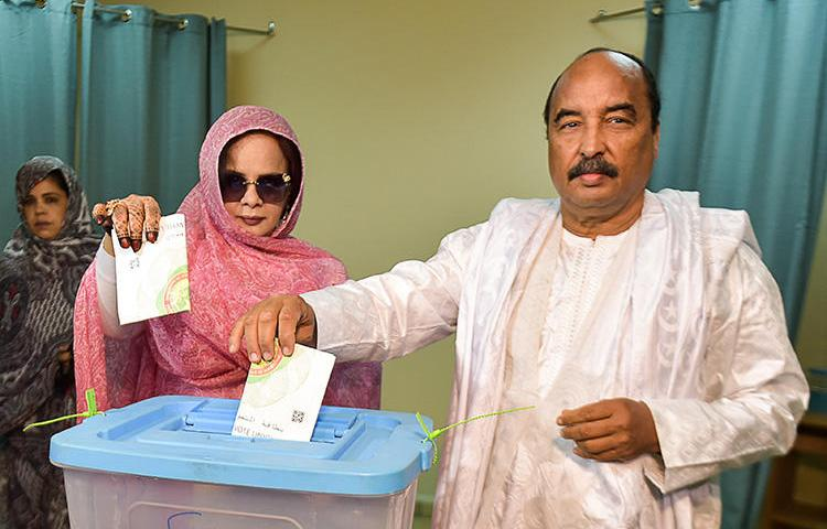 Mauritanian President Mohamed Ould Abdel Aziz (right) casts his ballot on June 22, 2019, at a polling station in Nouakchott during the presidential election. Mauritania freed blogger Mohamed Cheikh Ould Mohamed, who had been imprisoned since 2014, on July 29, 2019. (AFP/Sia Kambou)
