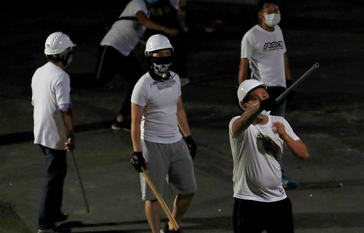 Men with poles are seen after attacking journalists and anti-extradition bill demonstrators at a train station in Hong Kong on July 22, 2019. (Reuters/Tyrone Siu)