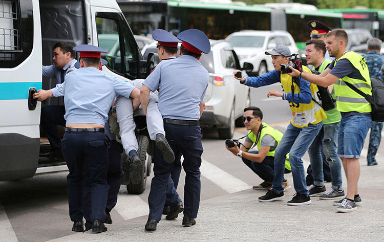 Police officers detain an opposition supporter as journalists take pictures during a protest against presidential election results in Almaty, Kazakhstan, June 10, 2019. The blocking of news websites during the leadership transition suggests that recent moves to control the internet are about censorship, not security. (Reuters/Pavel Mikheyev)