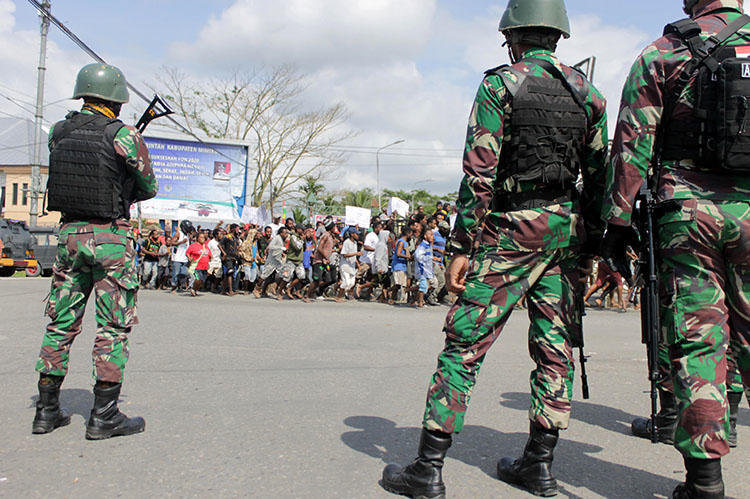 Indonesian soldiers stand guard during a protest in Timika, Papua province on August 21, 2019. Indonesia has ordered an internet shutdown in the region, restricting journalists trying to cover spreading violent protests. (AP Photo/Jimmy Rahadat)