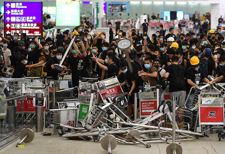 Pro-democracy protesters block the entrance to the airport terminals at Hong Kong's international airport on August 13, 2019. The protesters that day assaulted a journalist from China's Global Times at the airport. (AFP/Manan Vatsyayana)