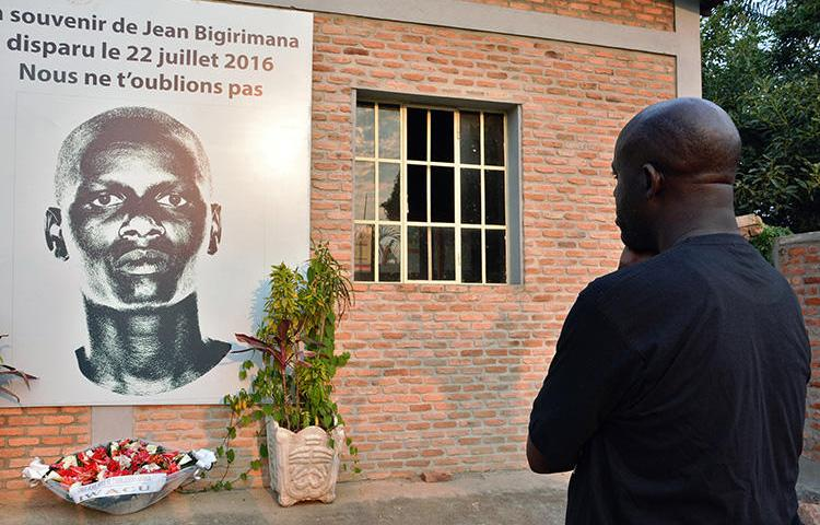 A man stands in front of a plaque in honor of missing Burundian journalist Jean Bigirimana in Bujumbura during a commemoration to mark one year after the journalist's disappearance on July 21, 2017. On August 2, 2019, CPJ joined a call for the U.N. Human Rights Council to extend the mandate of the Burundi Commission of Inquiry. (AFP/STRINGER)