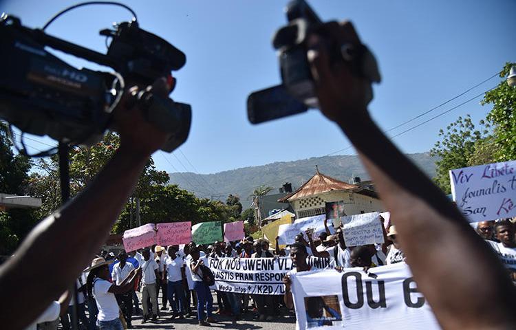 Des reporters haïtiens et d'autres personnes manifestent à Port-au-Prince le 28 mars 2018 pour réclamer des informations sur le photojournaliste disparu Vladimir Legagneur. Un autre journaliste, Luckson Saint-Vil, a été la cible de tirs dans le sud d'Haïti le 6 août 2019. (AFP/Hector Retamal)