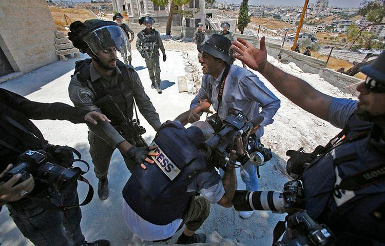 A picture taken in Dar Salah on August 2 shows Israeli border police scuffling with a journalist. At least 3 journalists were injured covering protests in Gaza and the West Bank on August 2. (AFP/Musa Al-Shaer)