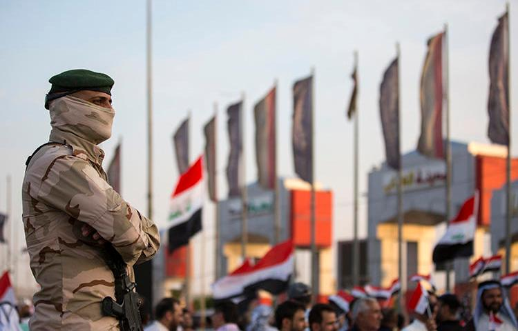 A member of the Iraqi security forces stands guard outside the Basra local government headquarters on July 19, 2019, as protesters gather for a demonstration. Basra police attempted to arrest Iraqi reporter Hassan Sabah in a raid on his home in Basra on July 23. (AFP/Hussein Faheh)