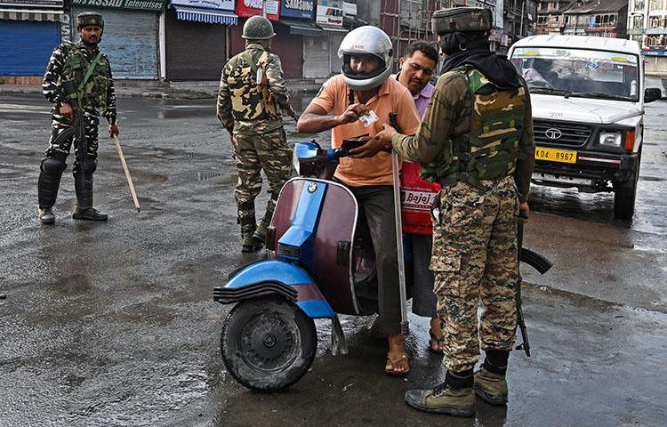 Indian security personnel check the identity of a motorist during a curfew in Srinagar on August 8, 2019, as widespread restrictions on movement and a telecommunications blackout are in place after the Indian government stripped Jammu and Kashmir of its autonomy. (AFP/Tauseef Mustafa)