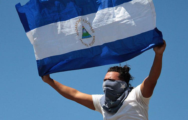 AUn manifestante despliega una bandera de Nicaragua en Managua, el 16 de marzo de 2019.  Periodistas que cubrían protestas antigubernamentales a lo largo del país fueron atacados, acosados y, en algunos casos, detenidos. (AFP/Maynor Valenzuela)