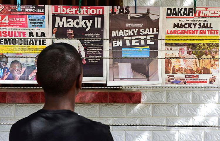 A man looks at newspaper front pages in Dakar, on February 25, 2019, one day after Senegal's presidential elections. Senegalese authorities arrested critical journalist Adama Gaye on July 29. (AFP/Seyllou)