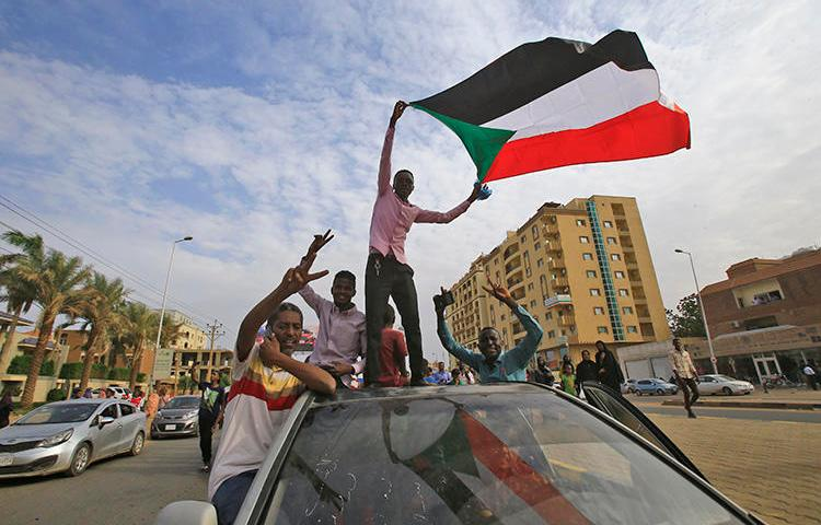 Sudanese protesters wave the national flag during a demonstration in the capital Khartoum on August 1, 2019. On July 24, authorities detained Al-Sayha newspaper editor-in-chief and journalists' union head Sadiq al-Rizaigi. (AFP/Ashraf Shazly)