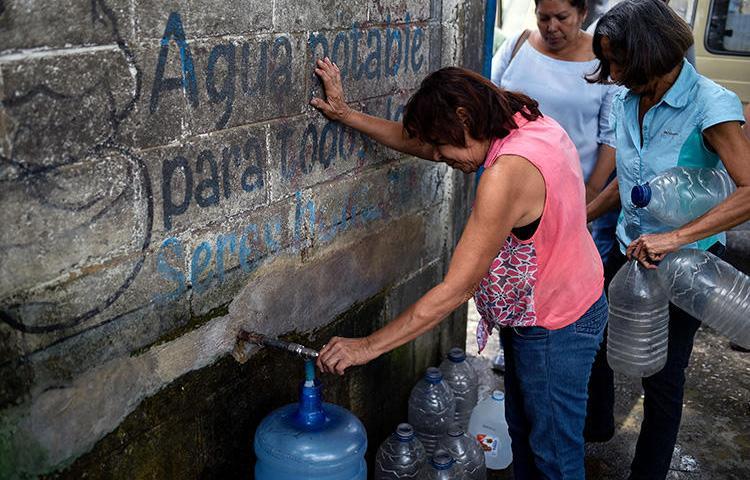 Una mujer llena un bidón de agua en una estación en San Juán de los Morros, Estado Guárico, Venezuela, el 10 de julio de 2018. El 18 de julio de 2019 un periodista fue detenido en San Juán de los Morros bajo la 'ley del odio' venezolana por criticar a un político regional. (AFP/Federico Parra)