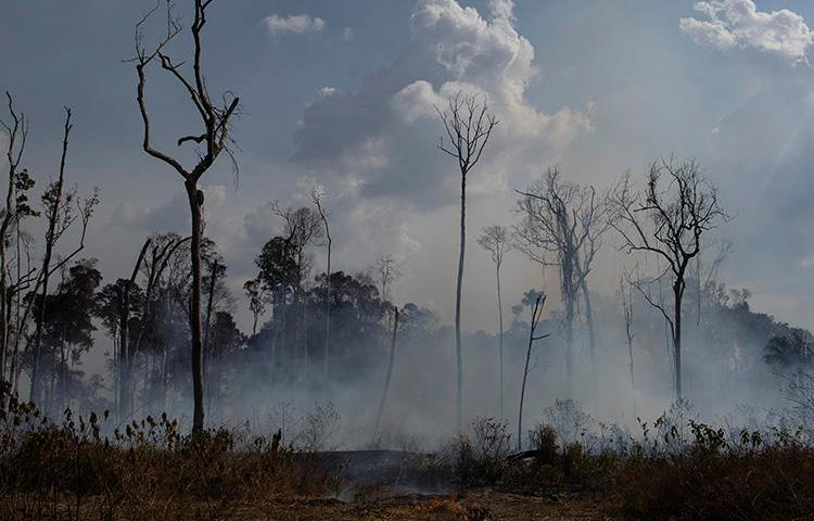 An area smolders in the Alvorada da Amazonia region in Novo Progresso, Para state, Brazil, on August 25, 2019. Brazilian journalist Adecio Piran was threatened on August 28 after reporting on fires in the region. (AP Photo/Leo Correa)