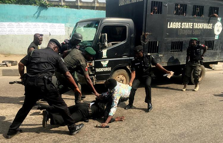 Police officers pull a journalist during an anti-government protest in Lagos, Nigeria, on August 5, 2019. At least four journalists were detained during the protests. (Reuters/Nneka Chile)