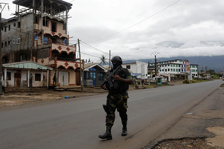 A Cameroonian elite Rapid Intervention Battalion member walks along an empty street in the city of Buea in Cameroon's Anglophone southwest region on October 4, 2018. Cameroon's military detained pidgin news anchor Samuel Wazizi on August 2, 2019, in Buea. (Reuters/Zohra Bensemra)
