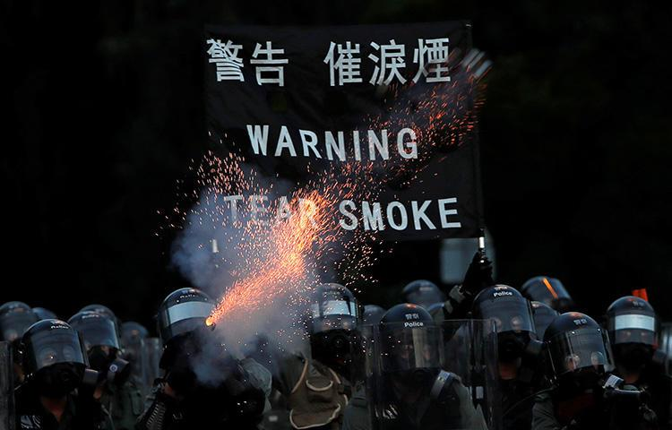 Police fire tear gas during protests in Hong Kong on August 5. A video journalist was knocked unconscious after being hit in the head by a tear gas canister while covering unrest in the Sham Shui Po district. (Reuters/Tyrone Siud)