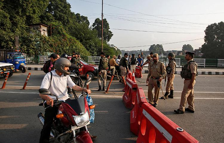Indian security personnel stop people during restrictions in Srinagar, in Indian-controlled Jammu and Kashmir state, on August 5, 2019. Indian authorities that day blocked the internet and communications networks in the region. (Reuters/Danish Ismail)