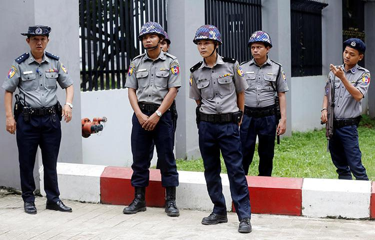 Police stand guard outside a court in Yangon, Myanmar, on August 9, 2019. The Mandalay District Court recently agreed to hear an appeal that could reopen a criminal defamation lawsuit against editor Swe Win. (Reuters/Ann Wang)
